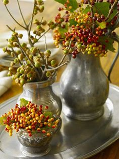 The patina of tarnished pewter contrasts with fall foliage in this rustic-meets-refined grouping. Tuck acorns, viburnum, and crab apple cuttings in a trio of staggered-size containers, corralling on a tray.