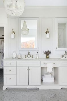 White cottage bathroom is lit by a white beaded chandelier hung over gray marble herringbone floor tiles and nickel and white glass sconces mounted beside white framed inset medicine cabinets.