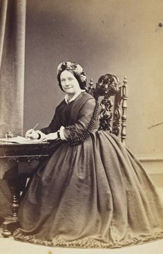 Miss Eliza Jane Thornton, Housekeeper to Queen Victoria at Windsor Castle from 1855 to 1865, and at Buckingham Palace from 1865. Seated at a writing desk, with a pen in her hand, facing the viewer.