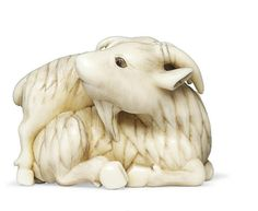 An Ivory Netsuke  Signed Ranmei, Edo Period (19th century)  Of a recumbent goat and young, eyes inlaid in pale and dark horn, Kyoto School