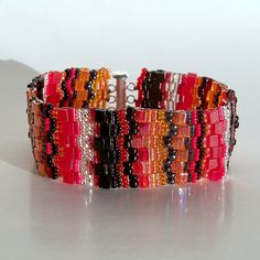 Beautifully handcrafted bracelet in black, red, orange and silver.    7 1/4 Inside circumference when clasped    1 Wide    Clasp - Silver Plated Brass Slide Clasp    CharmedGifts.etsy.com ~ Quality Handcrafted Jewelry and Gifts Due to individual monitor settings, actual color may vary slightly from that shown on your screen.