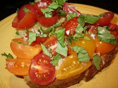Bruschetta alla Julie and Julia – Recipe    4 slices rough textured bread, such as focaccia, or from a crusty baguette, cut lengthwise  16 oz. assorted heirloom type tomatoes (I used President's Choice Rainbow heirloom cherry tomatoes) chopped and seeded if the seeds look sketchy  extra virgin olive oil  1 clove garlic, peeled and halved  sea salt  chopped fresh basil