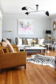 We mixed traditional, mid century modern, hollywood regency, antiques, and new furnishings to create a very layered and lovely space. It is a great example of how to mix old and new. We achieved layered texture with the zebra cowhide rug, sheep skin throws, leather on chairs, the vintage Howard Parlor upholstery, and velvet blush and animal print pillows.