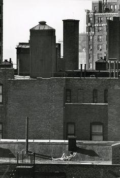 André Kertész – Untitled (woman sunbathing on roof reading)1964
