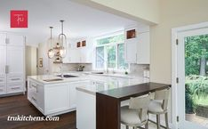 In the kitchen, Glacier white cabinets from Grabill Cabinetry in their Devonshire door style are used throughout the space. Beautiful Carrara Luce quartz countertops and backsplash offer an element of texture. A beautiful wood waterfall countertop from Grothouse pops in the space and is a nod to the home's wooded surroundings. Waterfall Countertop, Transitional Kitchen, Quartz Countertops, Carrara, White Cabinets, Backsplash, Kitchen Remodel, Kitchen Design, Texture