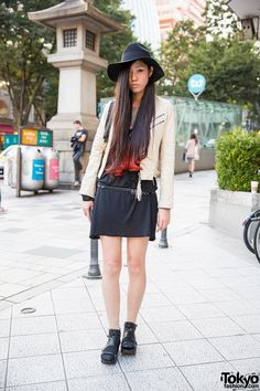 This is Showko, a long-haired girl with a cool style. She's a director. She is wearing a belted little black dress with a leather biker jacket on top, a big hat, black Givenchy bag and socks with studded leather sandals. She is also wearing a leather bracelet, a chain bracelet, a watch, golden rings and polka dot nail art.