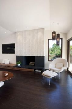 San Francisco Modern Home by J. Weiss Design >>>  Love the creme Heath Ceramics tile over the fireplace and the creme wool upholstery on the womb chair and ottoman.