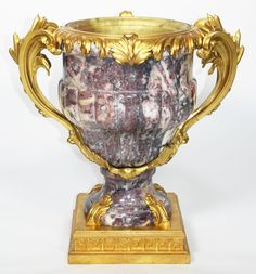A Very Fine French 19th/20th Century Louis XV Style Ormolu-Mounted Fleur de Pêcher Marble Vase/Urn with a tapering ovoid body applied with a pair of scrolled handles cast with acanthus-sheathed bulrushes, on a spreading foot and square plinth with acanthus clasps. Attributed to François Linke (1855-1946). Circa: Paris, 1900. The present vase is after a single example carved in porphyry, formerly in the collection of the Duc de Tallard. At the sale of Tallard's collection in 175...