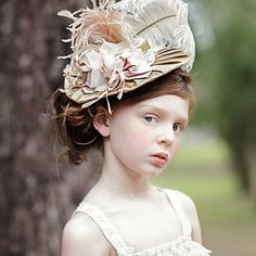 This hat is one you would have seen Marie Antoinette wearing to a garden party. Handmade using a wired buckram frame covered in silk with a hand pressed silk flower with vintage stamen. Adorned with a silk bow and a whimsical long ostrich plume. All in colors of champagne blush and cream.