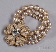 Vintage Imitation Baroque Pearl Flower Bracelet, Miriam Haskell, the clasp designed as a large flower centering a prong-set strass, with gilded metal petals covered entirely by imitation seed pearls, completed by three strands of imitation baroque pearls, lg. 7 1/2 in., signed.