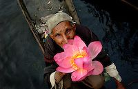 KASHMIR,INDIA: A Kashmiri vegetable seller holds a Kashmiri Lotus flower at the early morning market in Dal Lake in Srinagar. There has been less violence in Srinagar since a recent thaw in relations between nuclear-rivals India and Pakistan. More than 38,000 people have died in Indian Kashmir since the eruption of the anti-Indian rebellion in 1989. Human rights groups and separatists put the toll twice as high.