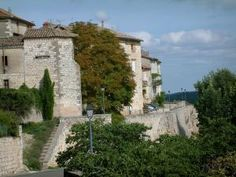 Castelnau-de-Montmiral - Lampadaires, arbres et maisons de la bastide, nuages dans le ciel