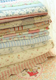 yummy stack of vintage quilts and ticking fabrics