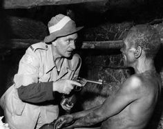 A British officer aims his revolver at a smiling suspected Mau Mau during a night raid. 1952, Kenya.