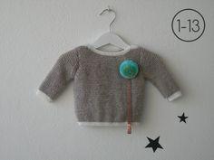 Jersey para bebe hecho a punto bobo en color arena con elástico, cuello y puños en color crudo. Sistema de cuelga – chupete mediante corchete.