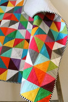 rainbow half square triangles quilts. Simple yet bold quilt with the perfect choice of binding fabric.
