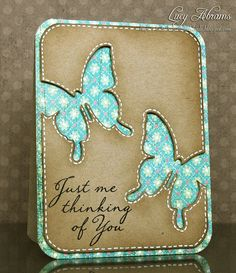 luv this look with kraft over aqua print and white stitching around the edges...negative space die cuts run off the page...