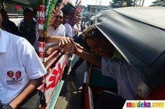Calon gubernur DKI Jakarta Faisal Basri berjabat tangan dengan pengendara Bajaj.