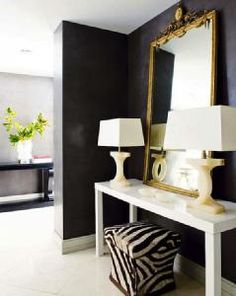 Entryway with Black wall, white glossy parsons table and zebra ottoman