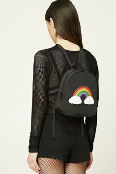 A structured mini backpack featuring a rainbow patch with fuzzy clouds, a zip front, a top handle, interior slip pockets, and adjustable buckled straps.