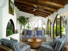 Natural light floods this Mediterranean sun room. Country blue-patterned cushions line the furniture, while arched windows and a wood plank ceiling lend to an architectural feel.
