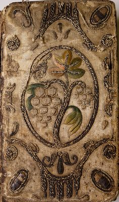 Embroidered Binding - Bible: English Authorised (1645-1646) White Satin worked in polychrome silk threads and gold braid and cord, to create a naturalistic representation of a Grape vine: the same design is depicted on both sides. In the centre within an oval of gold braid and cord is a spray of Vine, with two bunches of Grapes, three leaves and a tendril: the fruit and leaves worked in silk threads, and the stem in gold cord. Enclosing the oval is an arabesque...          ...