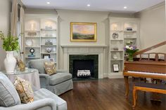 A traditional wooden piano and classic beige fireplace add formal sophistication to this traditional living area. Cozy pale gray armchairs lend an inviting feel to the space, ensuring it's fit for relaxation.