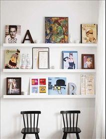 På tavellisterna i köket står en fin blandning av bilder och köksrelaterade föremål. Svarta barnstolar, Agam, Ikea.