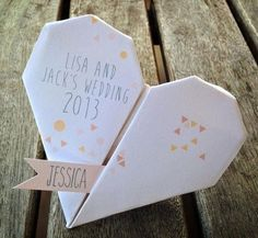 Folded hearts have been all the rage lately, because of their unique, angular shape. These muted place cards joyfully greet guests at their designated seats. | See more wedding origami and folded paper details: http://www.mywedding.com/articles/wedding-origami-and-folded-paper-details/: