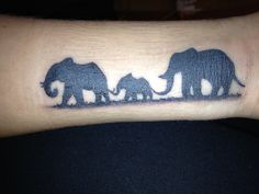 Elephant tattoo - third elephant smaller, sunset colors behind them, wrapped enough that the first elephant is holding the tail of the third