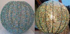 LUMINÁRIA, PENDENTE OU ABAJOUR REVESTIDO MISSANGAS. Modelo ESFERA. A estrutura do modelo é construída em aramado galvanizado com espessura precisa e pintada eletrostaticamente, nela é tramado manualmente o fio de cobre com missangas coloridas de vidro e poliéster.  Medidas: H 30 cm x L 35 cm.. Composição com 28 cores de Verde, Azul e Dourado sendo; 6 tons de dourados, 13 tons de azuis, 9 tons de verdes.