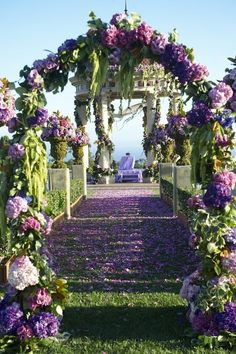 What a beautiful setting with gorgeous purple flowers and arches.Perhaps.this creative display is for a Wedding.What a lovely way for a couple to process up to the fine Stone Gazebo.