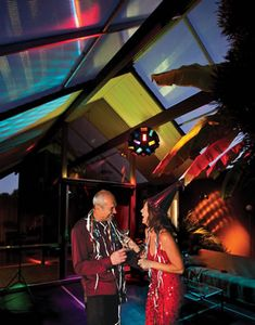 With colors swirling, Conny and Andrea Marx sip their drinks to the disco ball and music under the retractable roof of their Eichler atrium.