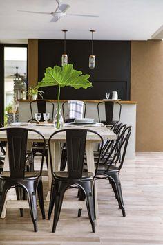 Casa en un country a la vera de un arroyo. Aquí, comedor al aire libre sobre porcelanato símil madera 'Legni Idéntica Acacia' (Ilva) y sillas metálicas con acabado mate (Raíz Negra).