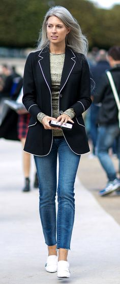 A white trim blazer, green sweater, jeans, and white sneakers