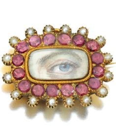 A GEORGIAN ANTIQUE LOVER'S EYE BROOCH. Rectangular brooch, inset with a portrait miniature of a gentleman's left eye, with blue iris, within a border of circular-cut garnets and half natural pearls, 1820s.