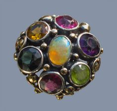 Dorrie Nossiter. Arts and Crafts ring.  Gold, silver, opal, tourmaline, peridot, citrine and garnet, c. 1930. Diameter: 1.90 cm (0.75 in). Ring case. Sold by Tadema Gallery. View 2.