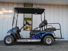 This 1998 E-Z-GO electric street ready custom golf cart is equipped with the street-ready package including premium lights, windshield, 4-panel rear view mirror, horn, and license plate bracket.  Plus, it has a high-performance motor, custom painted blue flame body, Line-X coated hard top, rear flip seat, digital charge gauge, aluminum diamond plate trim package, black dash kit with dual locking glove boxes, black seat covers, dedicated uncommon key switch, and chrome SS hubcaps.