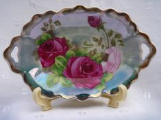 Perier Royal Vienna Handpainted Porcelain Dish Roses. Measures 7 3/4 by 5 by 1 tall.    The dish is signed by PERIER and is trimmed in gold with