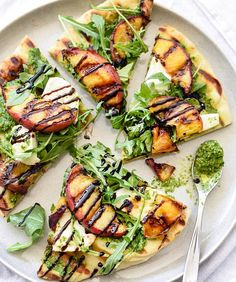 Grilled Flatbread with Peaches and Arugula: As if peaches weren't wonderful enough on their own, grilling them with a little balsamic vinegar draws out their natural sweetness.When layered with a zippy arugula pesto, these flatbread pizzas are poised to be the star at your next summer gathering.