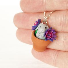 This miniature lop eared bunny is nestled in a real terracotta pot among tiny purple flowers. With a happy face, individually crafted flowers, and adorable sticky out ears, this piece will make you stand out and is sure to generate smiles. Lop Eared Bunny, Gifts For Pet Lovers, Polymer Clay Art, Flower Crafts, Jewelry Gifts, Jewellery, Handcrafted Jewelry, Handmade, Purple Flowers