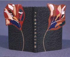 "Miniature design binding on Maurice Dufrere, Florilegium, Utrecht: The Catharijne Press, 1988 by James Reid-Cunningham. Full leather simplified binding with raised panels in the shape of flowers extending beyond the boards. Front bead silk endbands. Top edge graphite. Onlays of goat, kid and calf. Gold tooling and titling. Signed on the lower board. Stained tyvek clamshell box. 2 1/4"" x 1 3/8"". 5.6 x 3.5 cm. Bound in 1993."