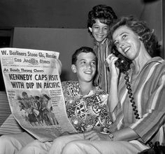 Eva Ban takes one of many phone calls after appearing on front page of the August 20, 1962 Los Angeles Times in a now-famous photograph of her in a bikini at Santa Monica beach exchanging grins with President Kennedy. Her son Peter is on left and her daughter Agi is in the background. (August 22, 1962)