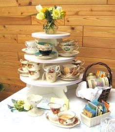 Stack teacups on a multi-tiered cake stand.