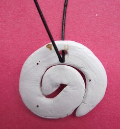 Bone carving necklace in koru shape made from clay  New Zealand