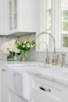 A polished nickel deck mount faucet is fixed beneath a window partially framed by white and gray herringbone tiles and over a farmhouse sink.
