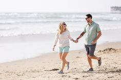 Light and airy engagement photo of a bride and groom running on the beach in San Diego by Cavin Elizabeth Photography