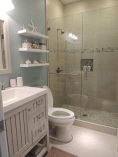Beach theme bathroom. Stone shower, floating shelves, shell decor
