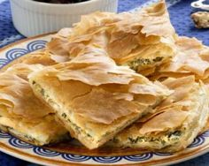Spanakopita, Greek spinach pie with feta cheese and filo party on a plate with Greek white wine, olives and walnuts Pita Recipes, Greek Recipes, Light Recipes, Snack Recipes, Cooking Recipes, Snacks, Greek Spinach Pie, Spinach And Feta, Frozen Food Delivery