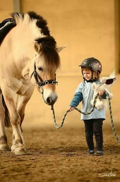 Kid walking horse with his stuffed animal in one hand an the horse in the other, adorable!